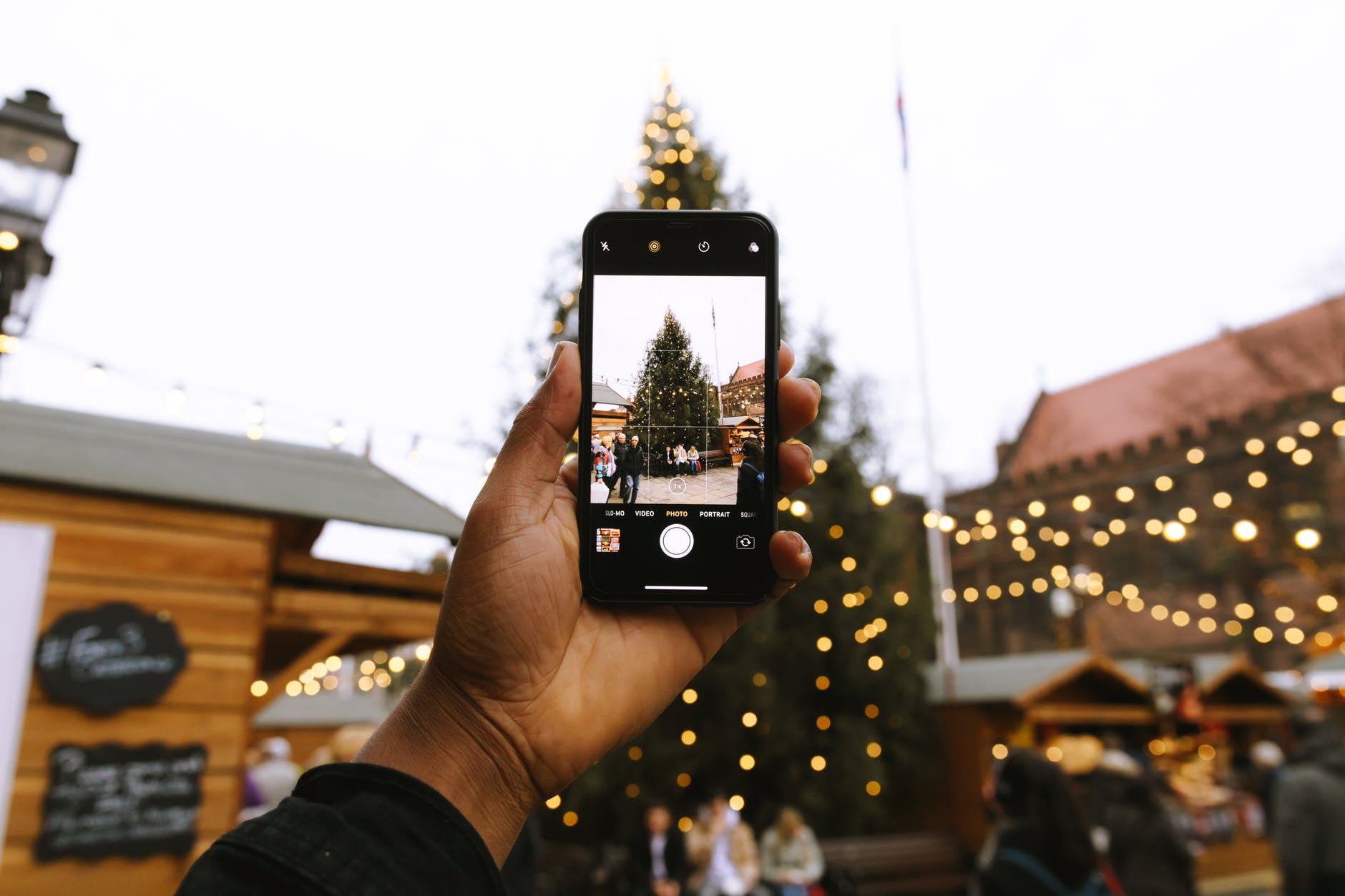 person taking photo of christmas tree using android smartphone