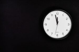 black round analog wall clock on black background